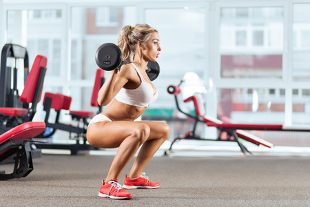 woman lifting weights: Sportive woman doing squatting with a barbell in the gym Stock Photo