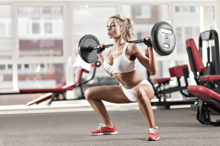 levantar pesas: Mujer juguetona que hace en cuclillas con una mancuerna en el gimnasio