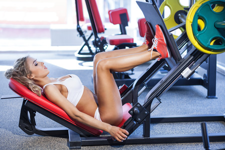 woman legs: Sportive blonde using weights machine for legs at the gym Stock Photo
