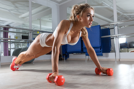athletic: Woman push-ups on the floor at the gym Stock Photo
