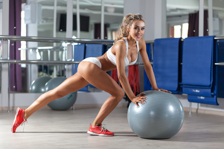 Young smiling woman doing exercise with ball at the gym