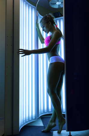 Woman in a red brassiere getting tan in the solarium