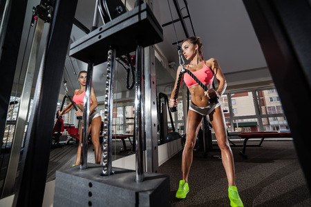 tough woman: Tough woman doing exercise with pull-down machine at the gym
