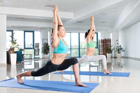 pilates studio: Two young women training in yoga asana in the gym Stock Photo