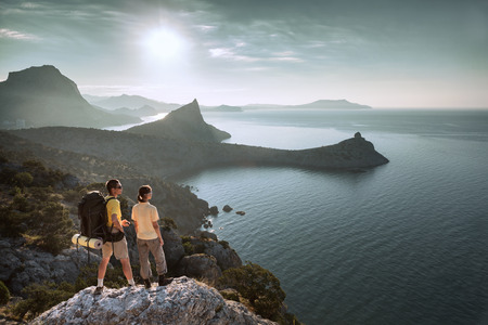 Couple is walking a mountain and looking at sunrise above the sea