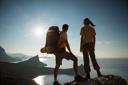 Tourist couple is walking a mountain and looking at sunrise above the sea