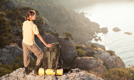 sunrise mountain: Woman with backpack on a mountain and looking at sunrise