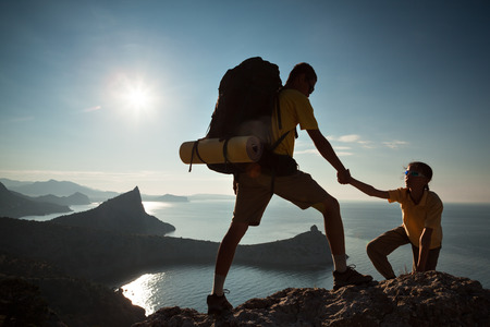 Backpacker helps to his friend to climb to roc