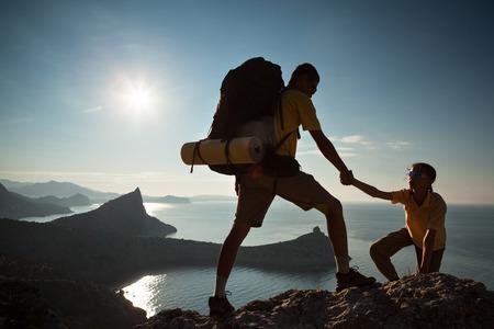 escalando: Backpacker ayuda a su amigo a subir a roc