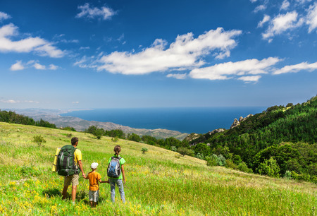 Happy family walking with backpacks on field and looking at the sea Foto de archivo