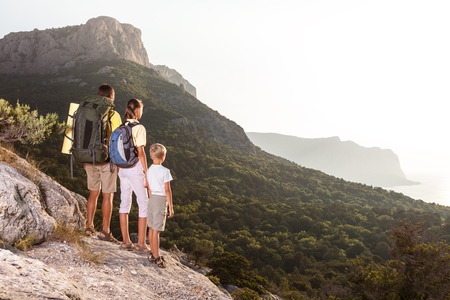 Happy family is walking with backpacks on mountains in the evening