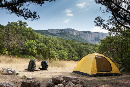 Two backpacks and tent against mountain