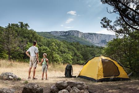 Vader en zoon op de camping en kijken naar de berg Stockfoto