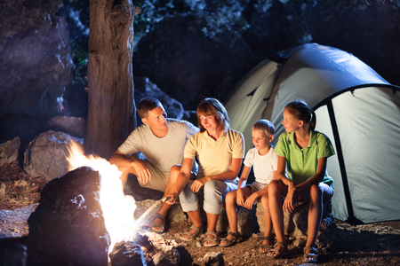 Family camping with campfire at night