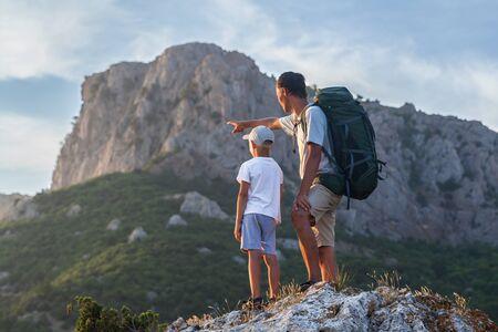 バックパックで父が大きな山に彼の幼い息子を示しています