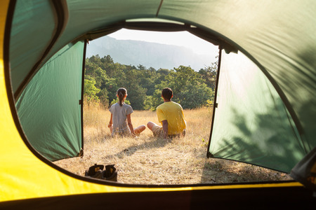 camping tent: Couple in a camping in the summer. View through open tent