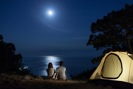 camping tent: Silhouette of couple close to tent looking at moon at night above sea Stock Photo
