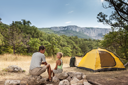 Father with little son in the summer camping on a meadow