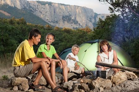 acampar: Familia cerca de la hoguera. Tienda de campaña y de montaña están detrás de ellos