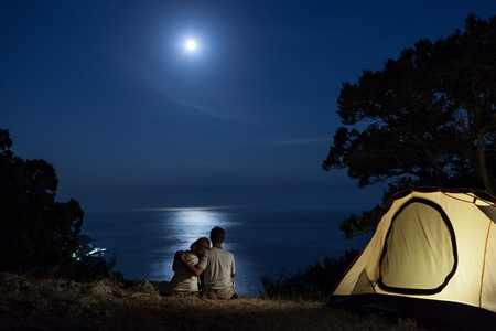 blue romance: Couple close to tent looking at moon night above sea Stock Photo