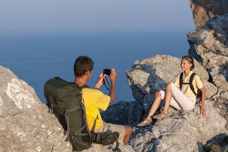 compact camera: Hiking couple on the rock. Man takes photo of woman by compact camera.