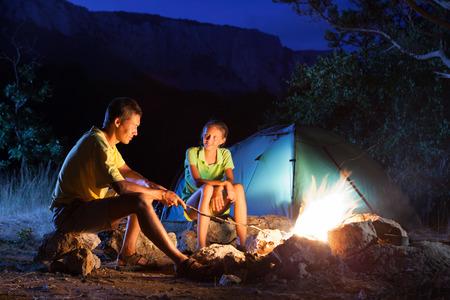 campamento: Pareja en el campamento con fogata en la noche Foto de archivo