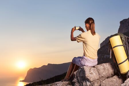 compact camera: Young woman taking photo of sunset in a mountain using compact camera Stock Photo