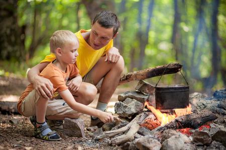 キャンプファイヤーの近くでキャンプで息子と父