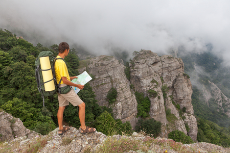 researches: Hiker researches a way using a map at the mountains