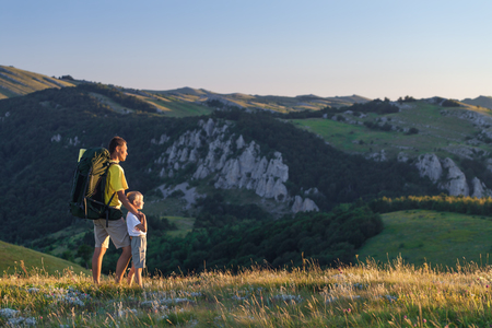 trekking: Father and his son hiking at mountains in the summer Stock Photo
