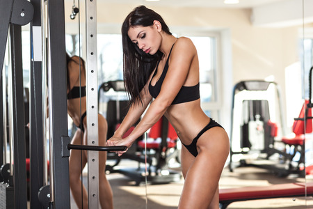 Young sexy woman dressed in black clothes at the gym Stock Photo