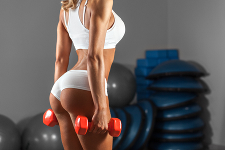 girl in sportswear: Strong sexy woman is training with dumbbells at the gym