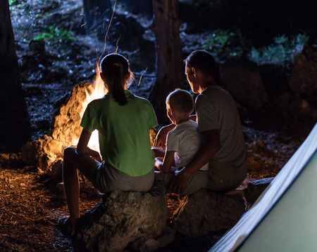 bonfire night: Family in the camping at night near campfire