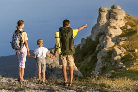 thee: Family of thee people walking on the mountains on the summer
