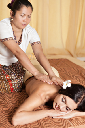 massagist: Asian massagist doing massage for caucasian woman in spa salon