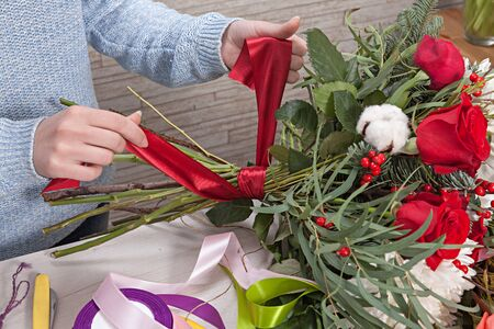 florists: Florists hand tying up fresh flowers with silk ribbon
