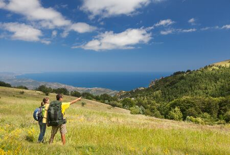 valley view: Couple with backpacks standing on green field and looking at the sea Stock Photo