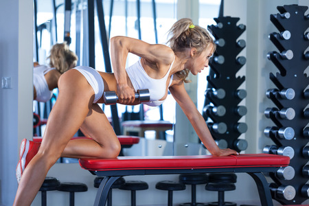 Attractive young woman lifting dumbbells in the gym