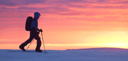 Skier walking on the mountain against brilliant sunset. Panoramic shot