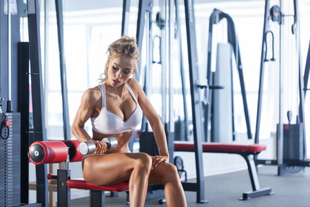 Pretty woman lifting dumbbells at the gym Stock Photo