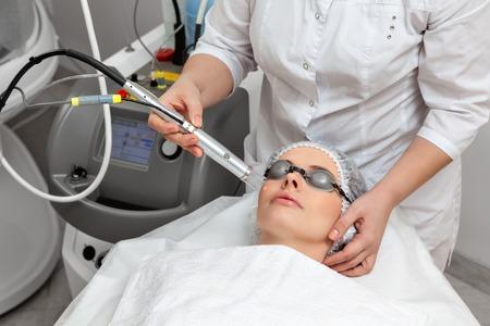 equipos medicos: Mujer tendida en una mesa con vasos de protección contra ojos que consiguen un tratamiento de la piel con láser en salón de belleza spa saludable