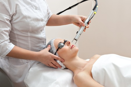 健康サロンでレーザー皮膚治療を得て目を保護するメガネをテーブルに横たわる女