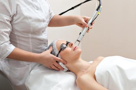 Mujer tendida en una mesa con vasos de protección contra ojos que consiguen un tratamiento de la piel con láser en salón de belleza spa saludable