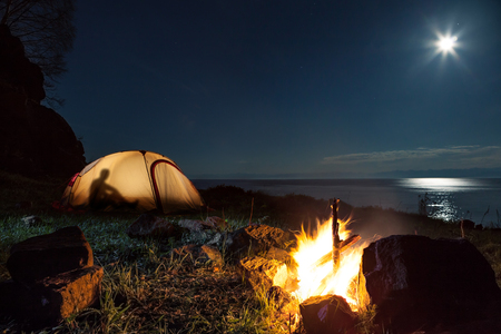 camping tent: Hiking tourists have a rest in his camp at night near campfire