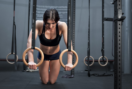 pullups: Young fit woman doing pull-ups on gymnastic rings. Muscular young female exercising with rings at gym. Stock Photo