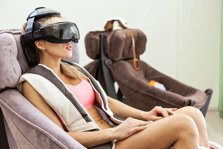 eye massage: Woman getting eye massage by special glasses at beauty salon Stock Photo