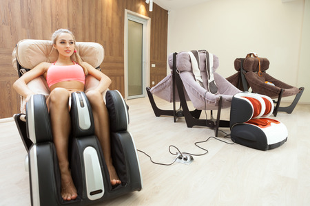 comfortable chair: Woman getting leg massage by special chair at beauty salon