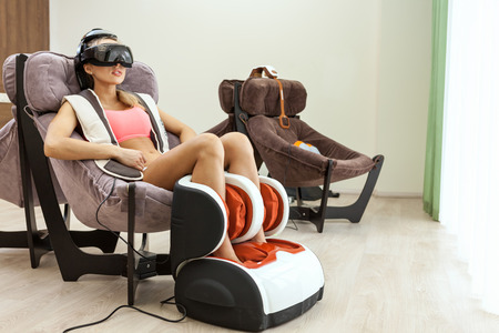 massage chair: Woman getting eye massage by special glasses at beauty salon Stock Photo