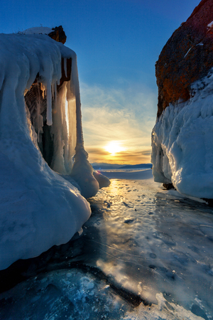 ice covered: Sunset through big icycles on ice covered Baikal Stock Photo