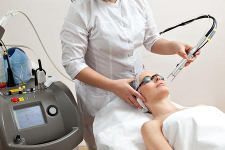 Mujer tendida en una mesa con vasos de protección contra ojos que consiguen un tratamiento de la piel con láser en salón de belleza spa saludable Foto de archivo